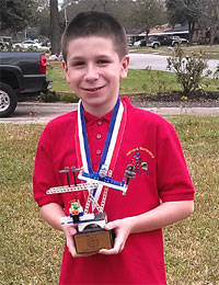 Noah poses with a trophy he won in a robotics competition.