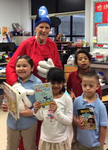 """HART member Judy Harwell, dressed up as Mickey Mouse from """"The Sorcerer's Apprentice,"""" hands out books at Burnet ES."""