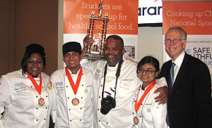 Westside HS students Jalien Noel, Jose Acosta, and Briseida Salas hoist the trophy in victory with Chef Reggie Martin and Ray Danilowicz