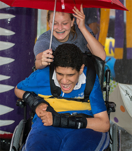 CECHS student Emerson Greer (holding umbrella) helps a Camp M.I. participant navigate a water activity.