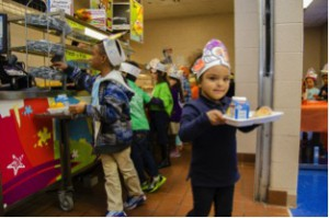 Kindergarteners at the School at St. George Place enjoy a Thanksgiving meal.