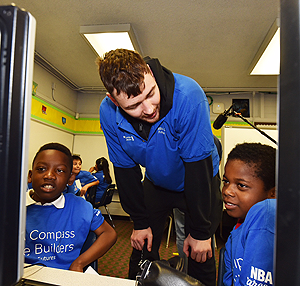 Houston Rockets power forward Donatas Motiejunas works with Rusk students on the EverFi Vault software to develop financial literacy.