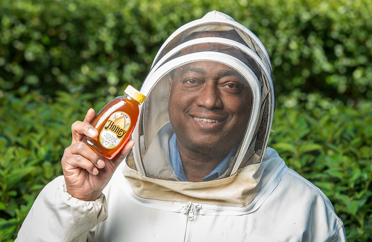 Anthony Dickerson poses in his beekeeping suit with a jar of his own honey.