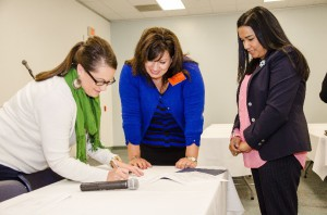 TDA Lead Monitors Kelly Craig and Sally Page sign the preliminary review report to Nutrition Services Senior Administrator Audene Chung.
